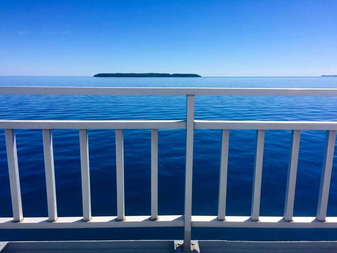Looking over a white fence on a ferry to Manitoulin Island