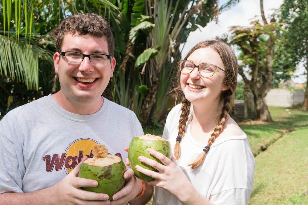Addie and Daniel holding coconuts and smiling