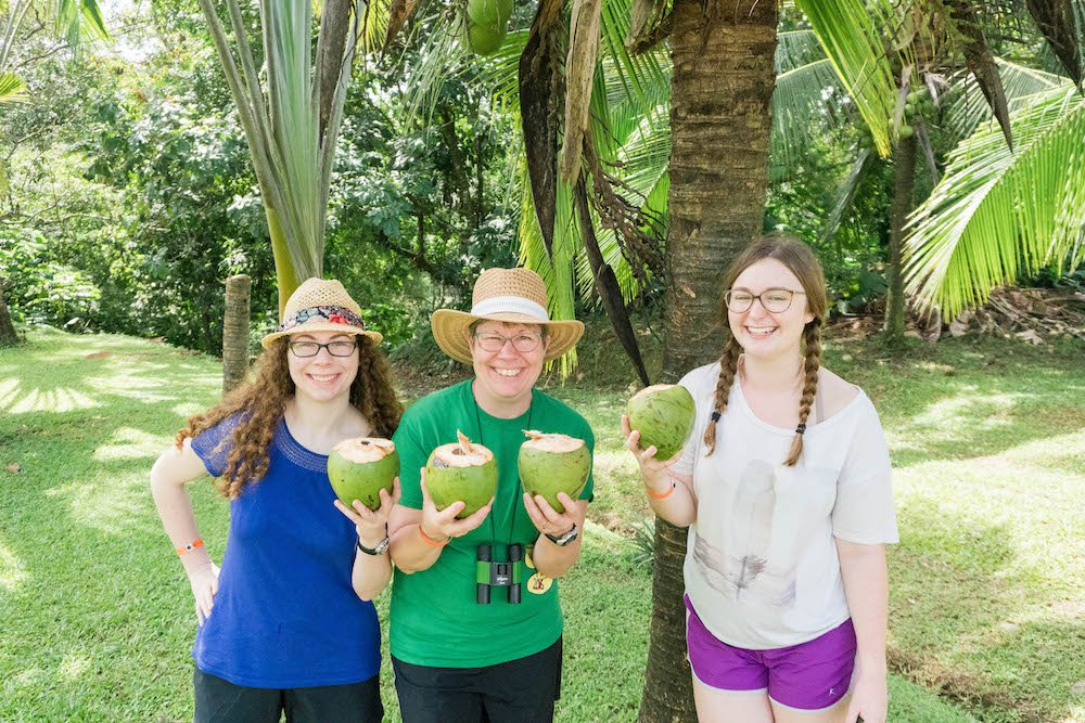 Isabel, Linda, and Addie holding coconuts under a palm tree