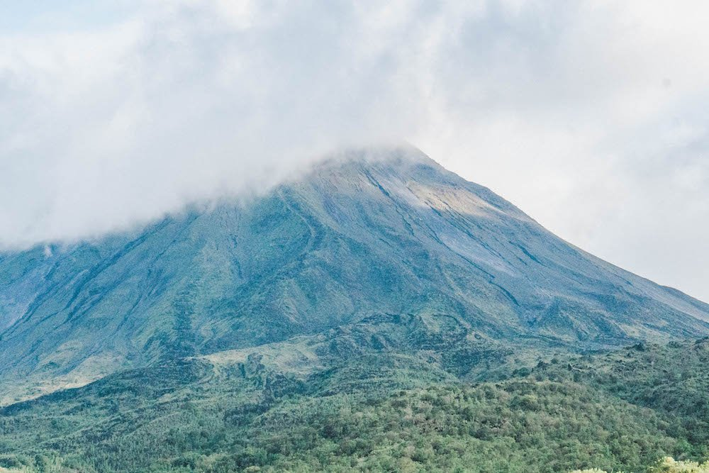 Arenal Volcano peeking through the clouds in La Fortuna, Costa Rica