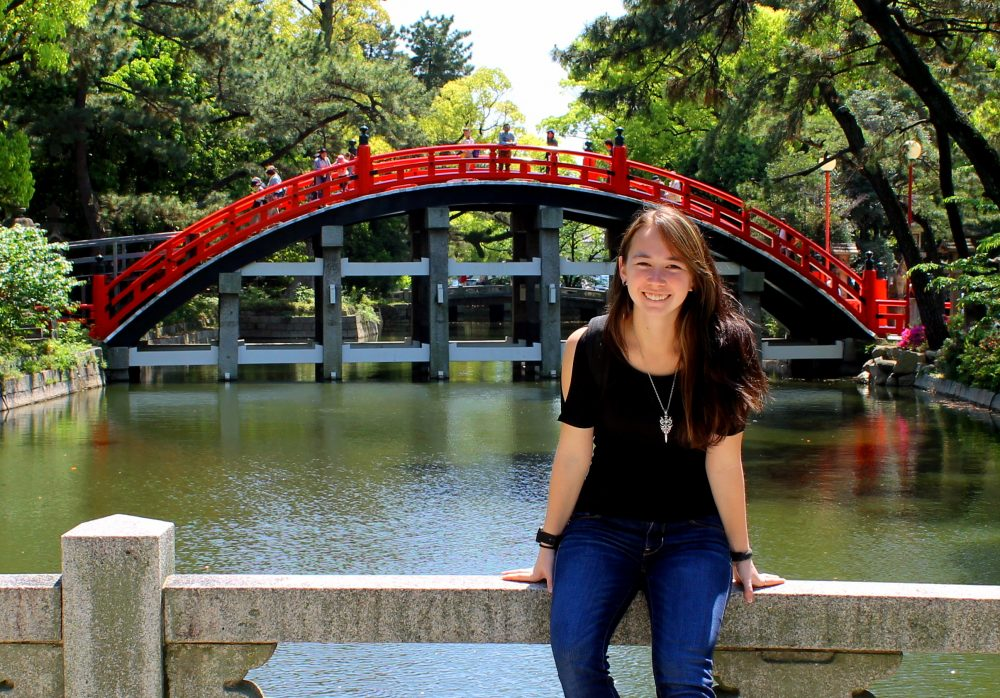 Kiyoko in front of a beautiful red bridge while studying abroad in Japan