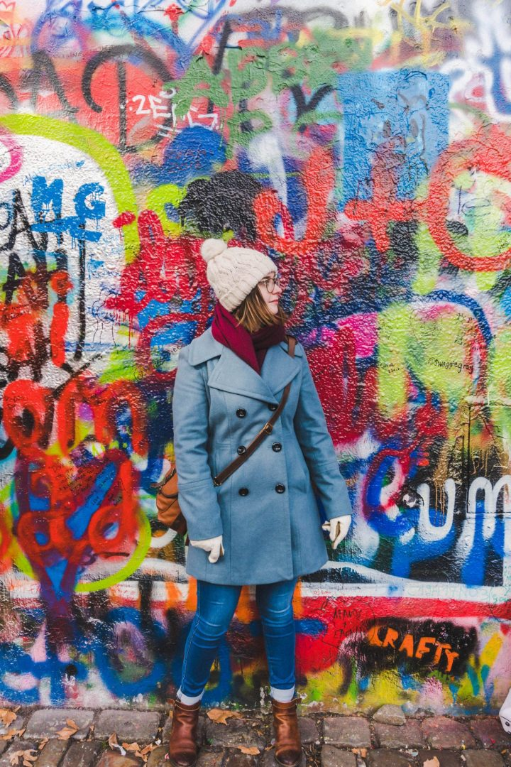 Girl in front of the graffitied Lennon Wall in Prague