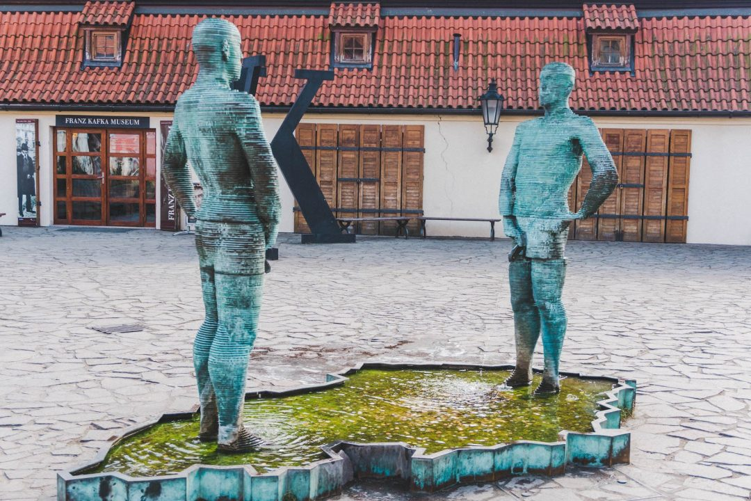 Two men peeing into a fountain shaped like the Czech Republic in front of the Kafka Museum in Prague