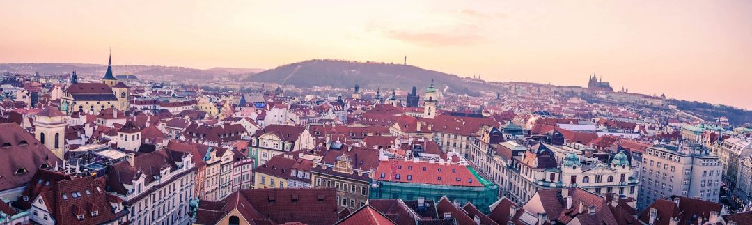 Panorama looking towards Petrin Hill over the roofs of Prague at Sunset