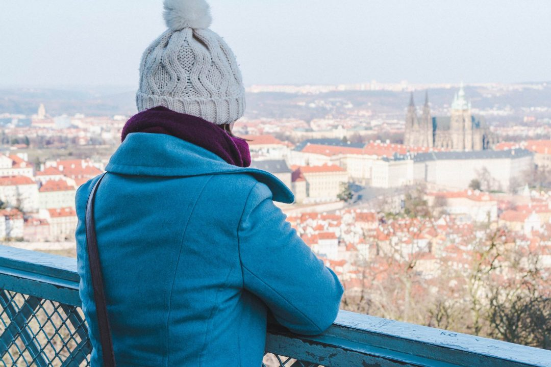 Girl in winter wear looking out at Prague Castle from Petrin Tower