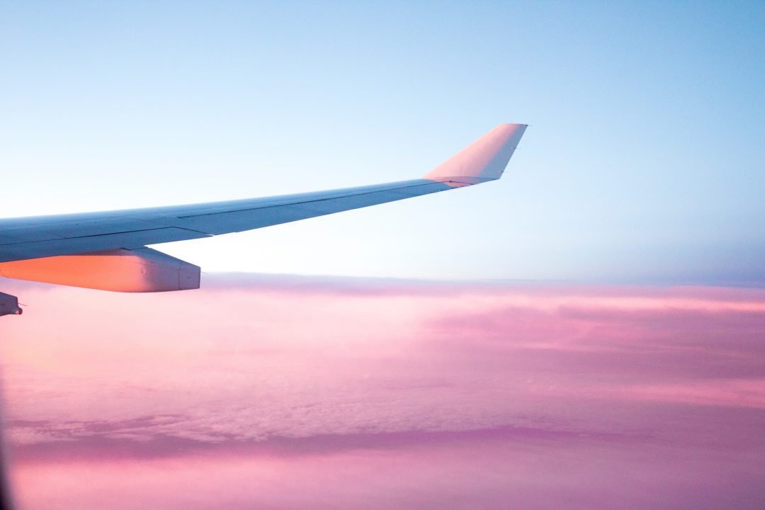 plane wing over pink clouds