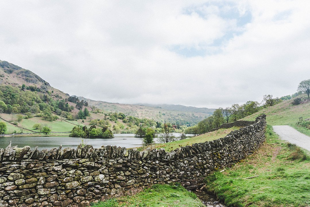 An old stone wall stretching across a field in the Lake District, UK