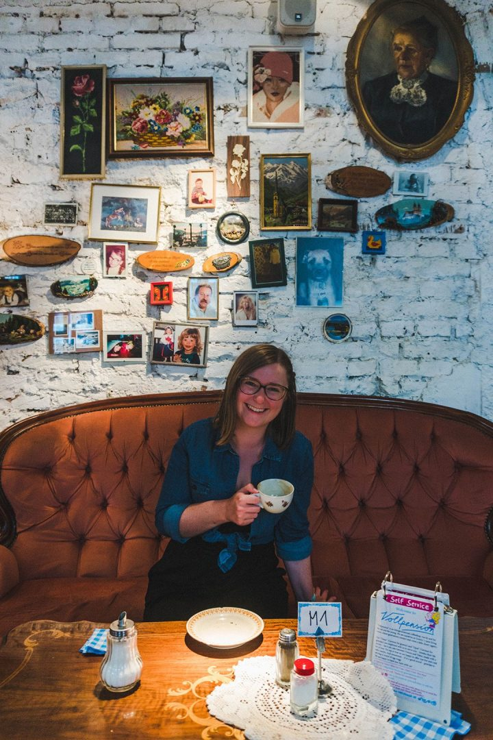 Addie with coffee in front of a wall of photographs at Cafe Vollpension in Vienna, Austria