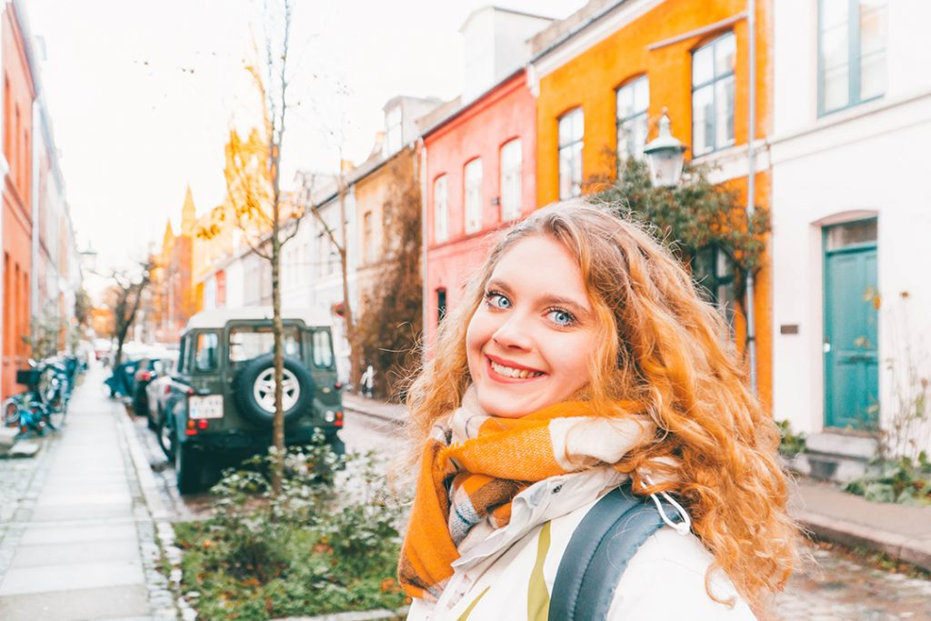 Megan smiling in front of colorful houses in Nyboder Copenhagen