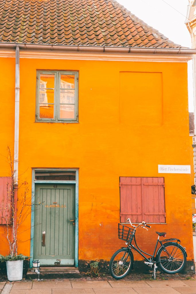 A bicycle outside of an orange house in Nyboder Copenhagen