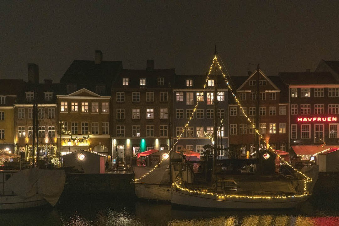 Boats in Nyhavn strung with Christmas lights in Copenhagen, Denmark