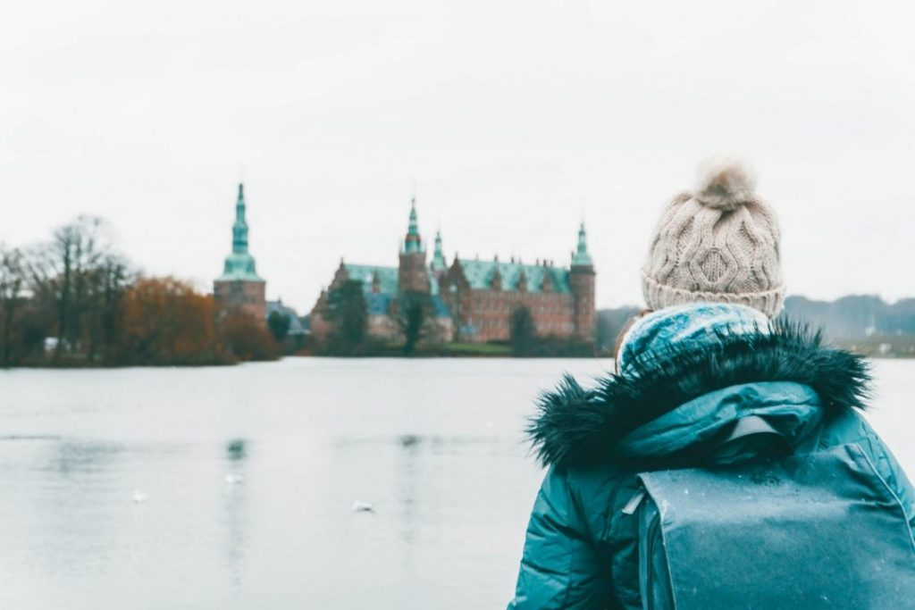 Addie staring out towards Frederiksborg Castle in a bobble hat